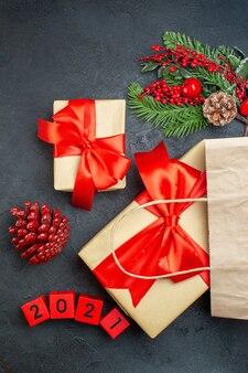 Widok pionowy świątecznego nastroju z szyszkami iglastymi i liczbami gałęzi jodły prezent na ciemnym stole