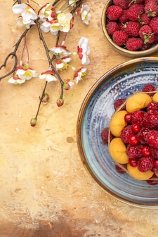 Widok pionowy świeżo upieczonego miękkiego ciasta z owocami i kwiatami herbatników na mieszanej tabeli kolorów
