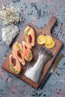 Widok pionowy świeżych ryb plasterki cytryny zielonego pieprzu na drewnianej desce do krojenia i nóż na niebiesko-czarnej tabeli mix kolorów