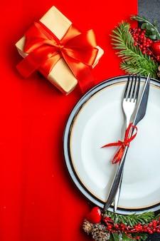 Widok pionowy tła xsmas z zestawem sztućców z czerwoną wstążką na talerzu akcesoria do dekoracji talerza jodły obok prezentu na czerwonej serwetce