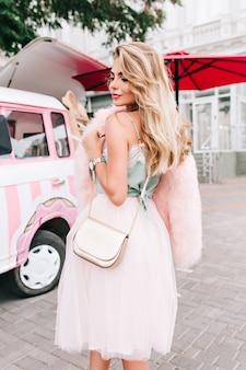 Widok pionowy z tyłu pin up girl w tiulowej spódnicy na tle retro samochodów. uśmiechając się w dół.