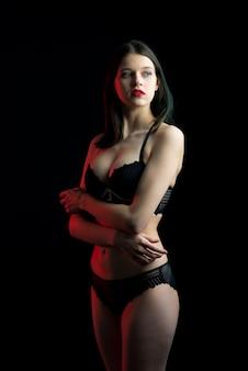 Widok pionowy zdjęcie piękna nieśmiała dama w koronkowym bikini typu buduar biustonosz. delikatny, chudy, szczupły kształt na białym tle czarnej przestrzeni.