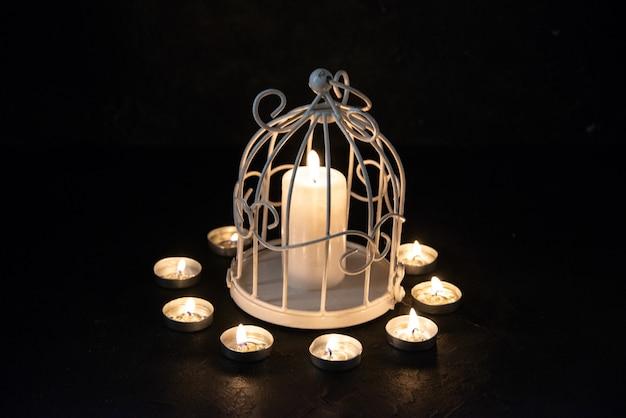 Widok płonącej świecy w lampie z przodu jako wspomnienie upadku na ciemną powierzchnię