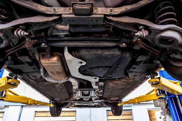 Widok podwozia samochodu podczas podnoszenia na podnośniku hydraulicznym w warsztacie