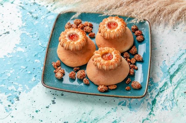 Widok połowy góry pyszne ciasta z ciasteczkami i słodkimi orzechami na jasnoniebieskiej powierzchni upiec ciasto biszkoptowe słodki cukier orzechowy