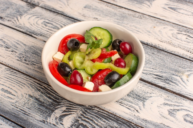 Widok połowy góry sałatka ze świeżych warzyw z pokrojonymi w plasterki ogórkami pomidory oliwka wewnątrz talerza na szarej powierzchni kolor sałatki z warzyw