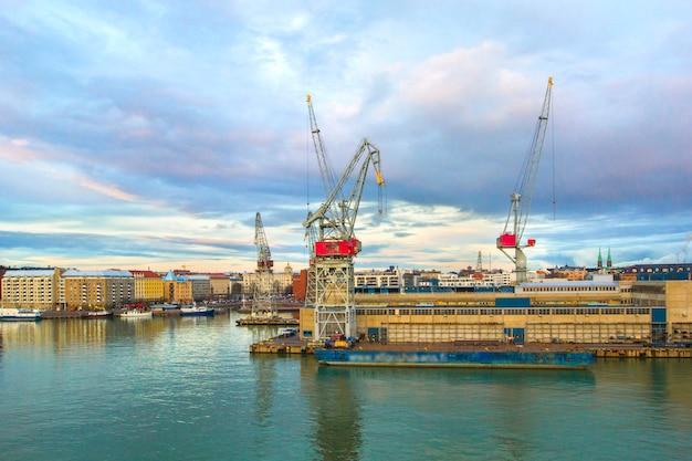 Widok port port helsinki z portowymi żurawiami, ładunkowymi zbiornikami i statkami w letnim dniu, helsinki, finlandia.
