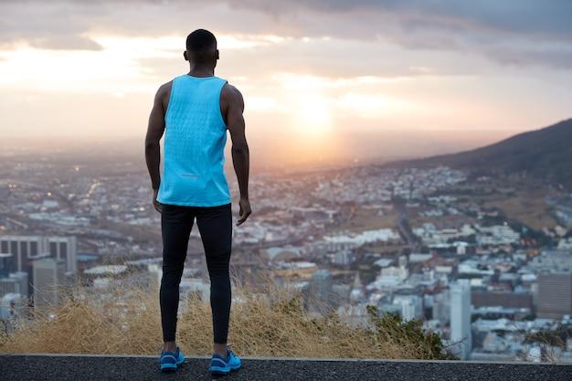 Widok poziomy atrakcyjnego mężczyzny ubranego w codzienne ubrania, który aktywnie biegał w pobliżu gór, cofa się, uważnie patrzy na piękny wschód słońca o świcie, oddycha świeżym powietrzem, czuje wolność, wolną przestrzeń