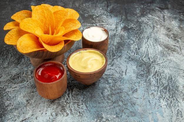 Widok poziomy chrupiących chipsów ziemniaczanych ozdobionych solą w kształcie kwiatu, majonezem i keczupem na szarym stole