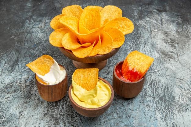 Widok poziomy domowej roboty chrupiące chipsy ziemniaczane ketchup majonez i sos na szarym stole