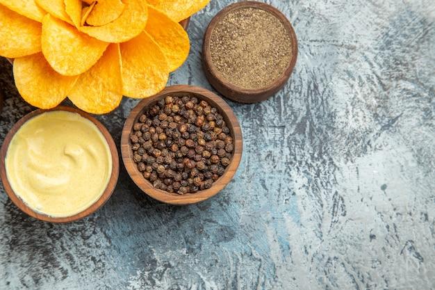 Widok poziomy domowych chipsów ziemniaczanych ozdobionych majonezem w kształcie kwiatu i różnymi przyprawami na szarym stole