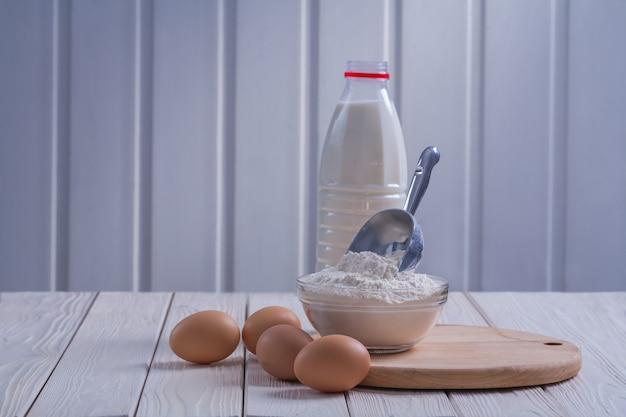Widok poziomy jaja mąki w misce miarka butelkę mleka