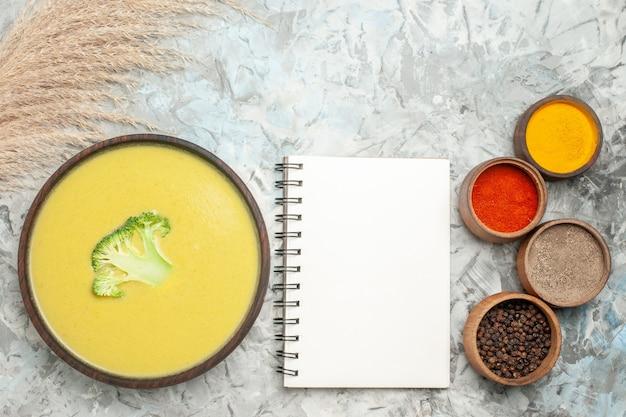 Widok poziomy kremowej zupy brokułowej w brązowej misce i różnych przypraw obok notebooka