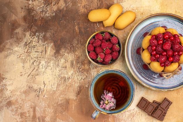 Widok poziomy miękkiego ciasta gorącej herbaty ziołowej z owocami batoników czekoladowych na tabeli mieszanych kolorów