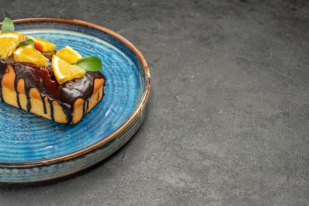 Widok poziomy miękkiego ciasta ozdobionego pomarańczową czekoladą na ciemnym stole