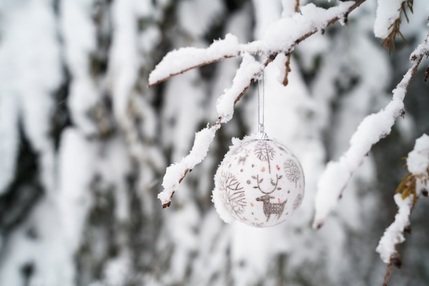 Widok poziomy ozdoba z reniferem zwisającym z sosny pokrytej śniegiem na zewnątrz.