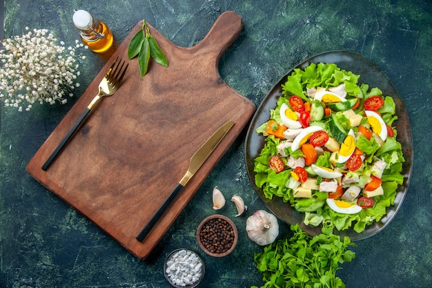 Widok poziomy pyszne sałatki z wielu świeżych składników przypraw butelka oleju czosnku sztućce na drewnianej desce do krojenia