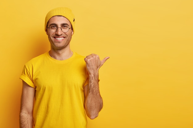 Widok poziomy szczęśliwy, zachwycony facet z zębatym uśmiechem, wskazuje kciuk od siebie, ma przyjazny wygląd
