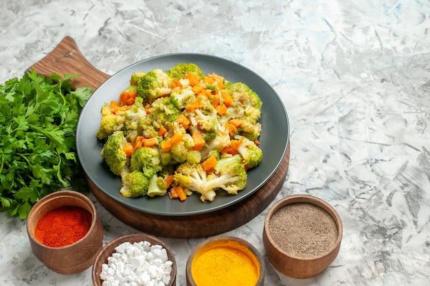 Widok poziomy zdrowe sałatki warzywne różne przyprawy i kilka zieleni na białym stole