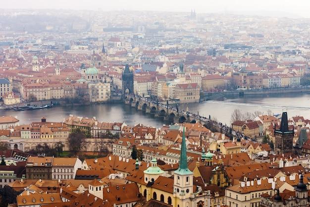 Widok pragi z wełtawą i mostem karola z zamku praskiego w deszczowy dzień