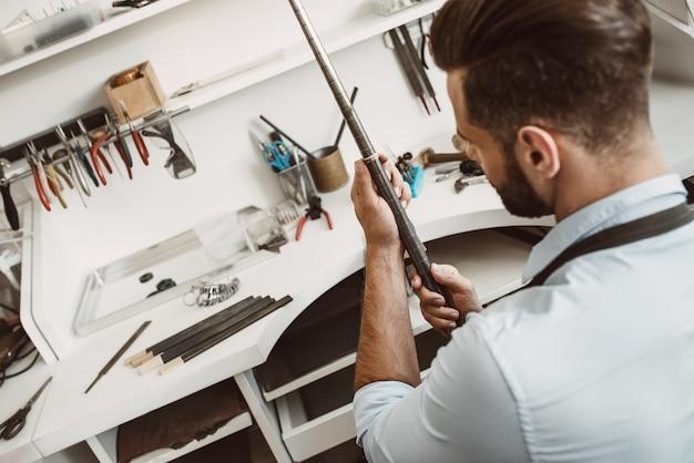 Widok prawego instrumentu z tyłu młodego jubilera płci męskiej sprawdzającego rozmiar pierścionka za pomocą specjalnego narzędzia w