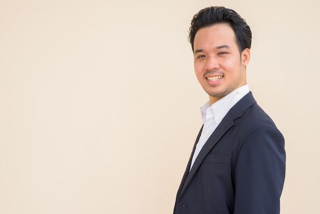 Widok profilu azjatyckiego biznesmena noszącego garnitur i uśmiechającego się na prostym tle