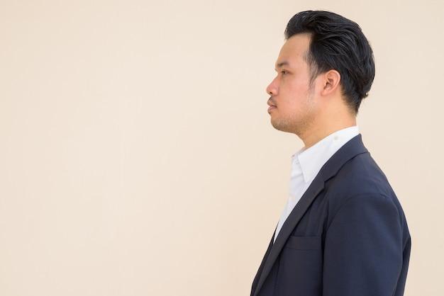 Widok profilu azjatyckiego biznesmena w garniturze na prostym tle