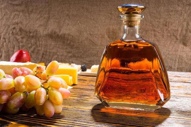 Widok profilu bocznego butelki alkoholu whisky na rustykalnym drewnianym stole z różnymi serami i winogronami z miejscem na kopię