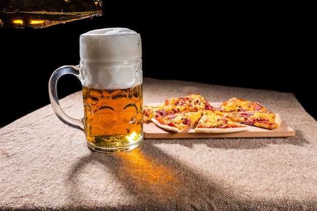 Widok profilu bocznego kufel piwa z pianką obok kawałków pizzy ułożonych na drewnianej desce do krojenia na powierzchni stołu pokrytej jutą