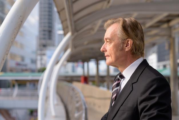 Widok profilu dojrzały przystojny biznesmen patrząc na widok na miasto