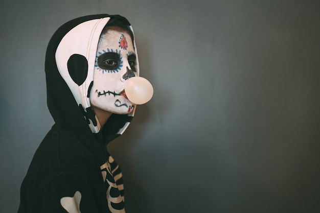 Widok profilu dziewczyny z makijażem i kostiumem martwej dziewczyny, który robi bąbelki z gumą do żucia