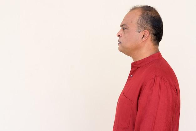 Widok profilu indyjskiego mężczyzny noszącego tradycyjne stroje przed zwykłą ścianą na zewnątrz