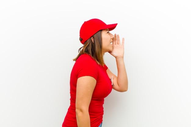 Widok profilu kobieta dostawy, patrząc szczęśliwy i podekscytowany, krzycząc i wzywając copyspace na stronie przeciwko biały