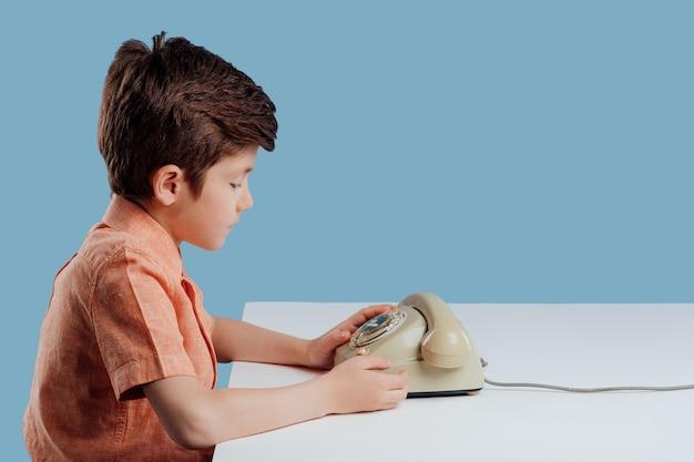 Widok profilu mały chłopiec i stary telefon siedzący przy stole na niebieskim tle