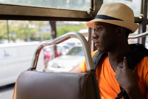 Widok profilu młodego turysty myśli i patrząc za okno podczas jazdy autobusem w bangkoku w tajlandii