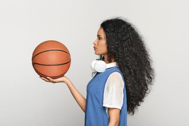 Widok profilu młodej czarnej kobiety w rekreacyjnej z długimi kręconymi włosami i słuchawkami na szyi trzymającej koszykówkę