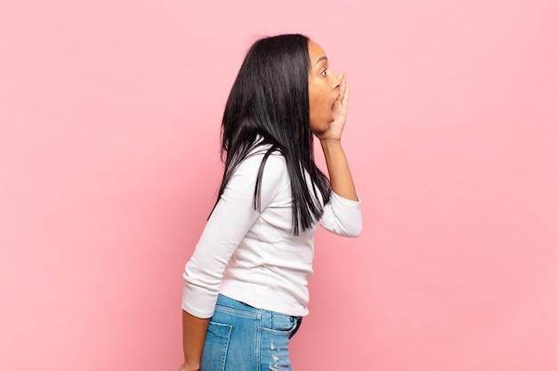 Widok profilu młodej czarnej kobiety, wyglądającej na szczęśliwej i podekscytowanej, krzyczącej i wołającej, by skopiować miejsce z boku