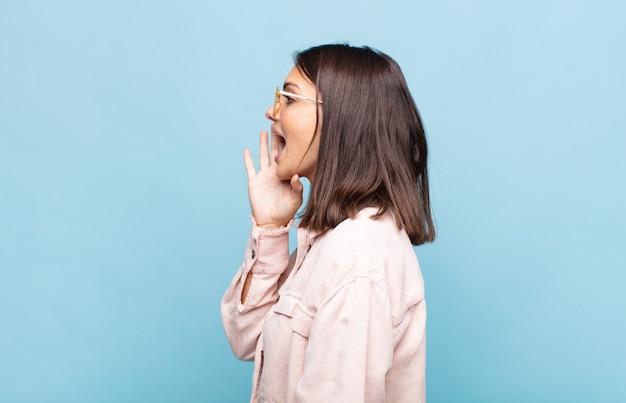 Widok profilu młodej ładnej kobiety, wyglądającej na szczęśliwej i podekscytowanej, krzyczącej i wołającej, by skopiować miejsce z boku