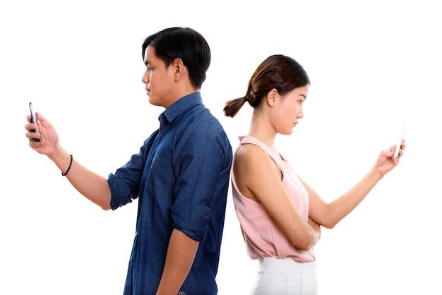 Widok profilu młodej pary azjatyckich przy użyciu telefonu komórkowego wraz z plecami przeciwko sobie