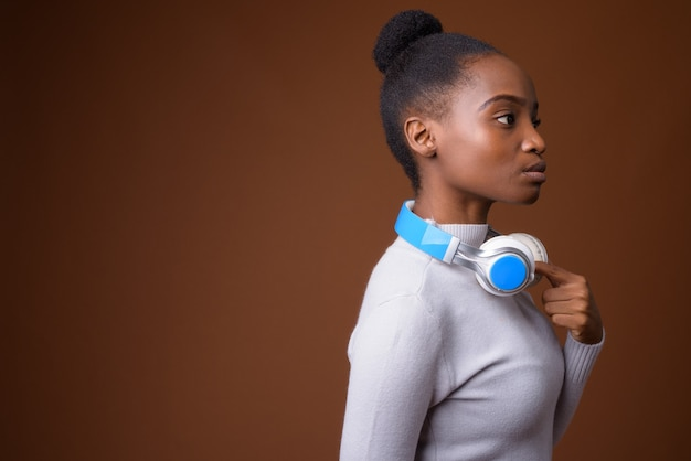 Widok profilu młodej pięknej kobiety afrykańskiego zulu ze słuchawkami