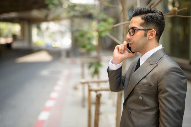Widok profilu młody przystojny biznesmen perski rozmawia przez telefon na ulicach miasta na zewnątrz