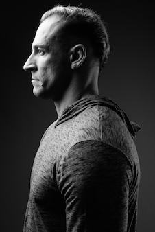 Widok profilu muskularnego mężczyzny w czerni i bieli