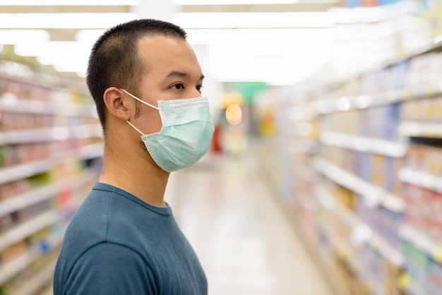 Widok profilu przeznaczone do walki radioelektronicznej młodego człowieka z azji z maską zakupy z odległości w supermarkecie