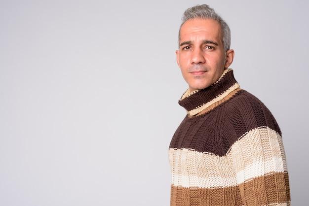 Widok profilu przystojny mężczyzna perski patrząc na aparat gotowy do zimy
