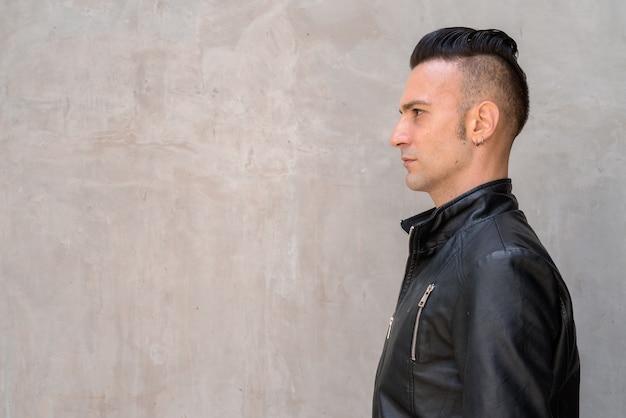 Widok profilu przystojny młody człowiek z podcięciem na sobie czarną skórzaną kurtkę