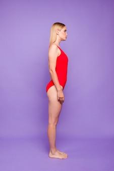 Widok profilu skoncentrowanej pani stojącej prosto na białym tle