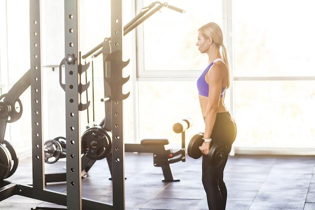 Widok profilu stojąca kobieta w siłowni, trzymając hantle. zdjęcia studyjne