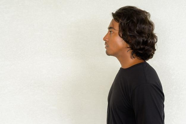 Widok profilu strzał przystojnego młodego indyjskiego mężczyzny na prostym tle na zewnątrz strzał z naturalnym światłem