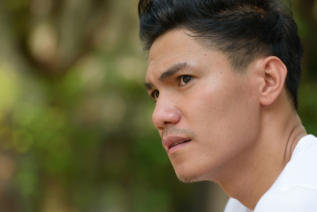 Widok profilu zbliżenie przystojny mężczyzna azji myśli na zewnątrz