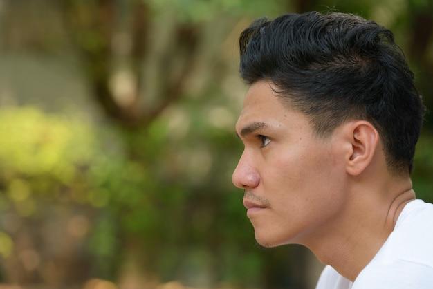 Widok profilu zbliżenie przystojny mężczyzna azji na zewnątrz